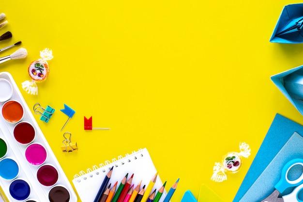 Канцелярские принадлежности школы красочные на желтом фоне с copyspace. Бесплатные Фотографии