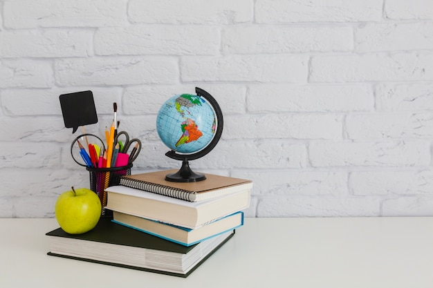 School composition with books, apple and world globe
