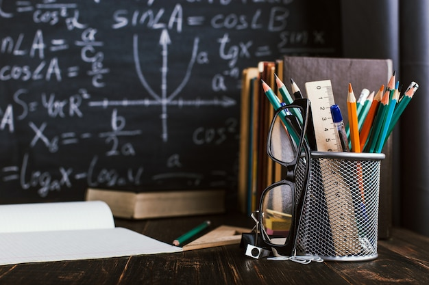 School desk in classroom, with books on background of chalk board with written formulas Premium Photo