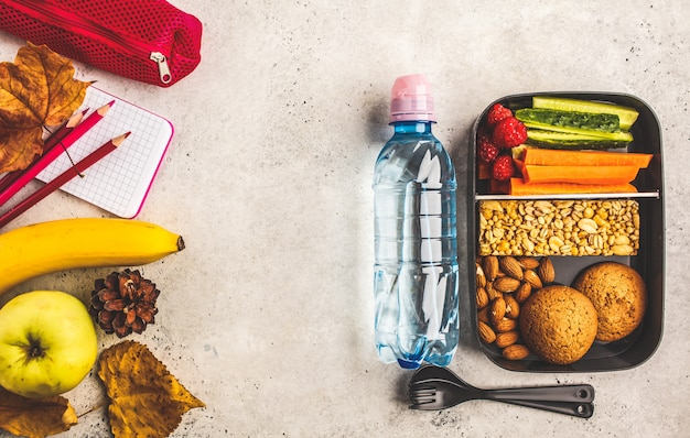 School flat lay. healthy meal prep containers with fruits, berries, snacks and vegetables. Premium Photo