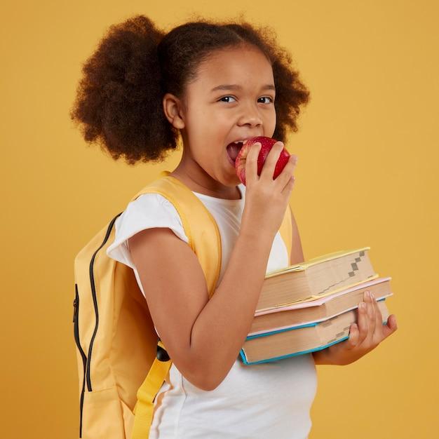 リンゴを食べて本を持っている女子高生 無料写真