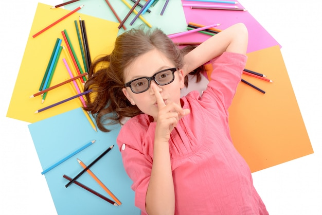 School girl lying on the floor with color pencils Premium Photo