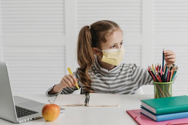 Школьница в медицинской маске и рисунок Premium Фотографии