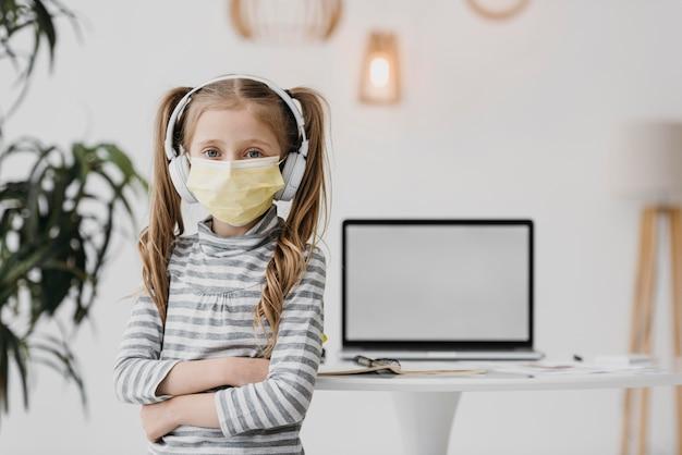Ragazza della scuola che indossa maschera medica al chiuso Foto Gratuite
