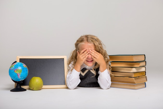 School girl with books and blank drawing board on white background Premium Photo