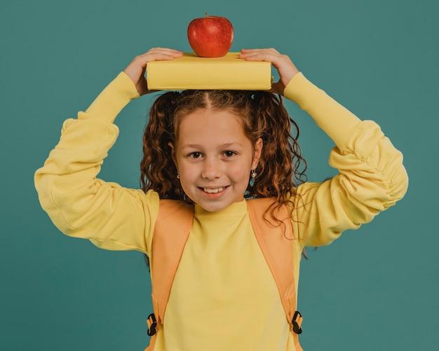 Школьница в желтой рубашке держит книгу и яблоко Бесплатные Фотографии