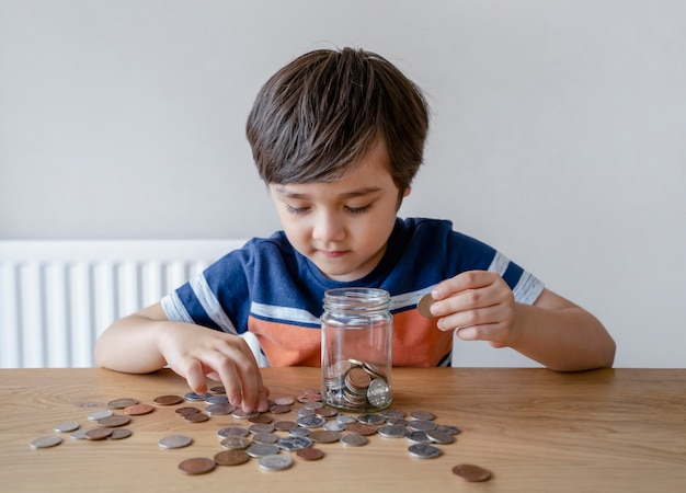 明確な瓶にお金のコインを入れる学校の子供、彼の節約したお金を数える子供 Premium写真