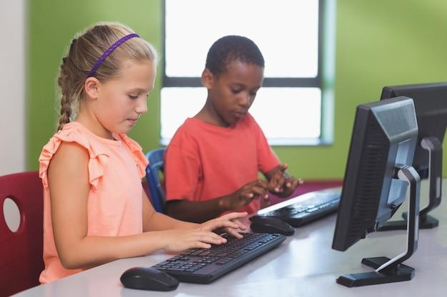 教室でコンピューターを使用して学校の子供たち Premium写真