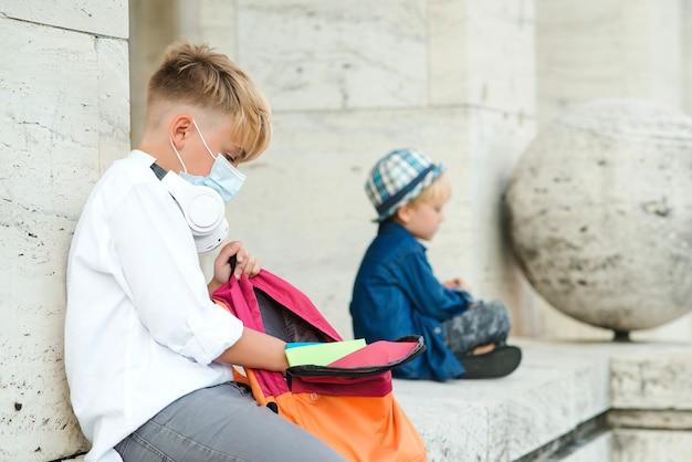 コロナウイルスの発生時にフェイスマスクを着用している学校の子供たち Premium写真