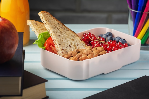 School lunch in a box, berries, nuts and a sandwich. Premium Photo