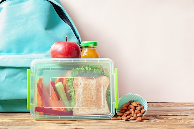 School lunch box with sandwich, vegetables, juice and almonds on table. Premium Photo
