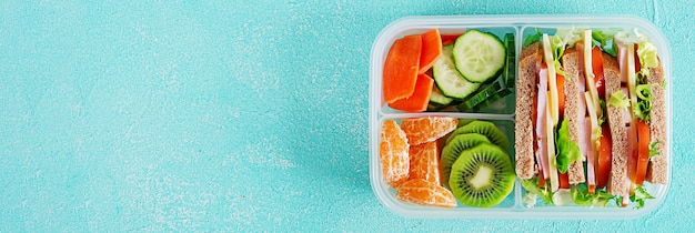 School lunch box with sandwich, vegetables, water, and fruits on table. Premium Photo