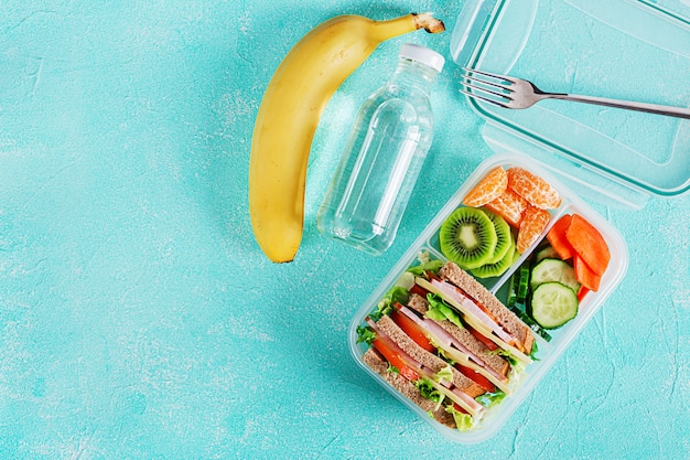 School lunch box with sandwich, vegetables, water, and fruits on table Free Photo
