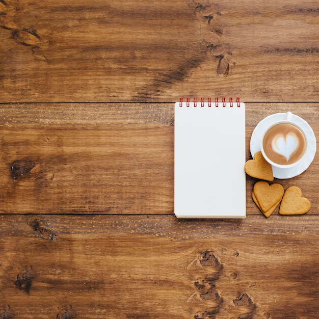 School notebook and coffee mug on a wooden background Free Photo