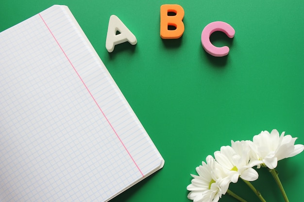 School notebook next to the letters abc and white chrysanthemums Premium Photo
