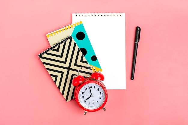 School objects like geometric notebooks, pen and alarm clock on pink Premium Photo