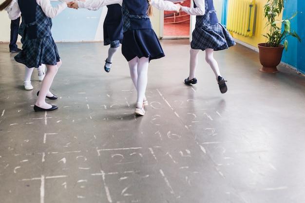 School and schoolchildren, children run on recess, rest between lessons, children's legs, development, warm-up, sports Premium Photo