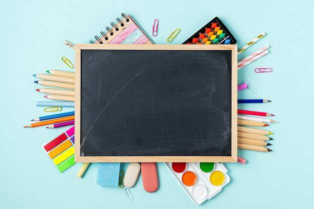 Школьные принадлежности на синем фоне доске Premium Фотографии