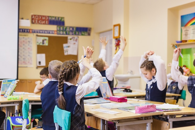 School and students, the child raised his hand to answer the teacher, friendship Premium Photo
