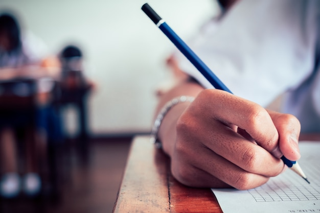 School students hands taking exams and writing examination with holding pencil in classroom Premium Photo