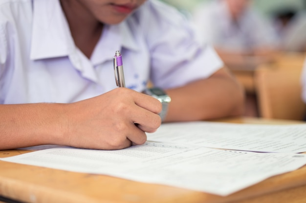 School students  taking exam writing answer in classroom with stress Premium Photo
