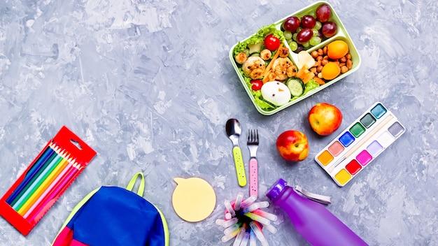Школьные принадлежности и ланч-бокс с едой для детей, копией пространства Premium Фотографии