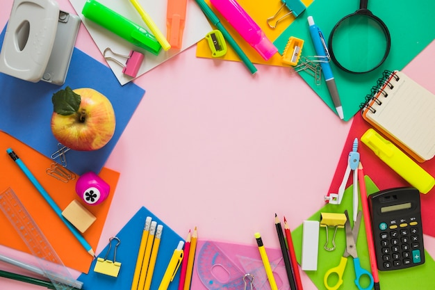School supplies and apple laid in circle Free Photo