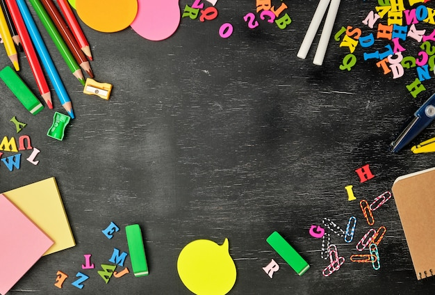 School supplies background with multicolored wooden pencils, notebook, paper stickers, paper clips Premium Photo