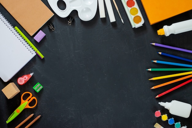 School supplies on black board background. back to school concept. frame, flatlat, copy space for text Premium Photo
