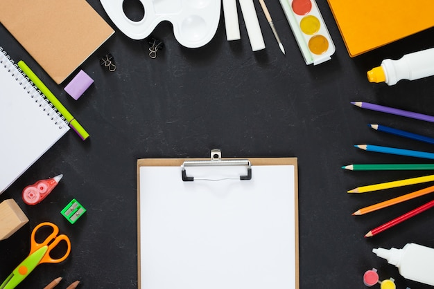 School supplies on black board background. back to school concept. frame, flatlay, copy space for text. mock up Premium Photo