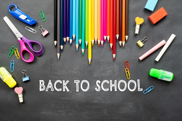 School supplies on black board background. back to school concept Premium Photo