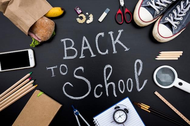 School supplies on blackboard with writing Free Photo