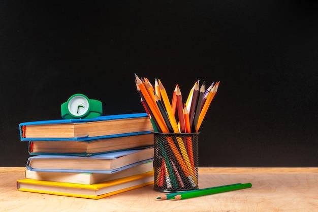 School supplies and books on black background Premium Photo