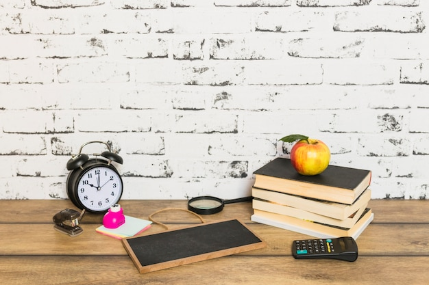 School supplies and books with apple on top Free Photo
