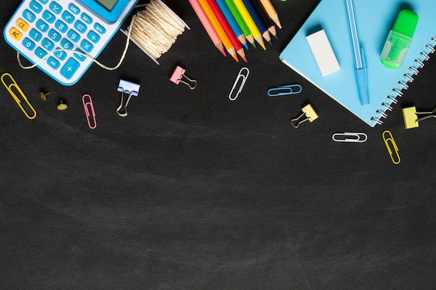 School supplies on a chalkboard Premium Photo