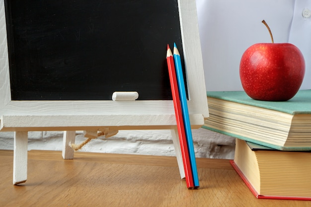 School supplies, miniature chalk board, a stack of books and an apple on the table Premium Photo