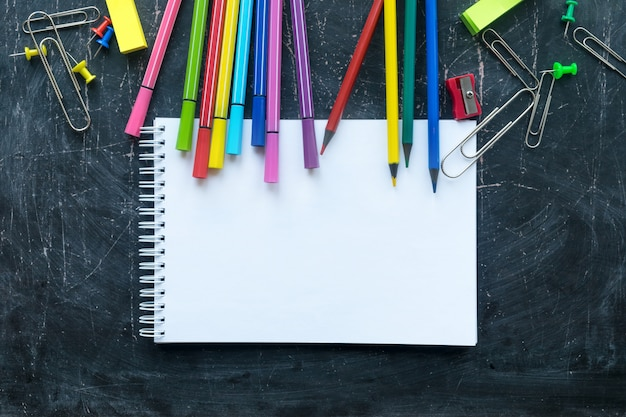 School supplies and notebook on a chalkboard background. free space for text Premium Photo