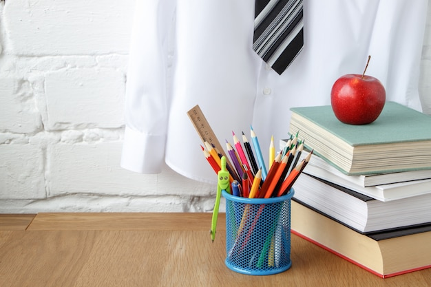 School supplies, a stack of books and an apple on the table Premium Photo