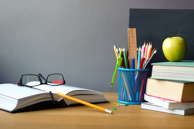 School supplies, stack of books, chalkboard and open book with glasses on a wooden surface Premium Photo