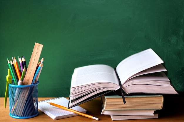 School supplies, stack of books, chalkboard and open book on a wooden surface Premium Photo