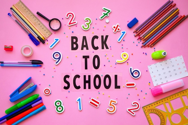 School supplies with back to school letters. back to school concept.  stationery and scrabble letters on the table. Premium Photo