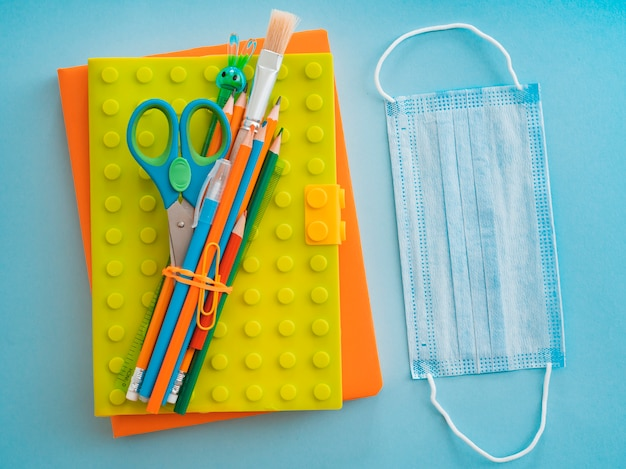 School supplies with medical face mask on blue blue. flat lay, top view, layout, template, free space Free Photo