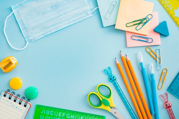 School supplies with medical face mask on blue. flat lay, top view, layout, template, free space Free Photo