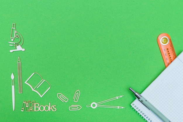 School supplies wooden miniatures and notebook with ruler and pen on green background Premium Photo