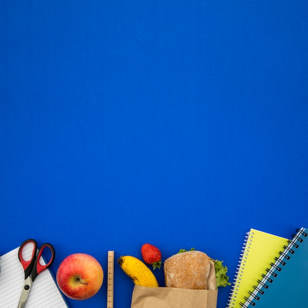 School things and sandwich on blue background Free Photo