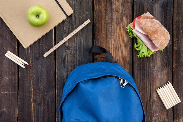 Schoolbag, sandwich and stationery on table Free Photo