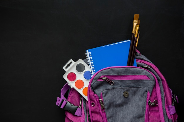 Schoolbag with brushes, watercolors and copybook Free Photo