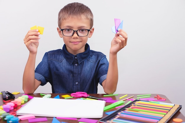 Schoolboy in a blue shirt sitting at the table. boy with glasses. concept back to school Premium Photo