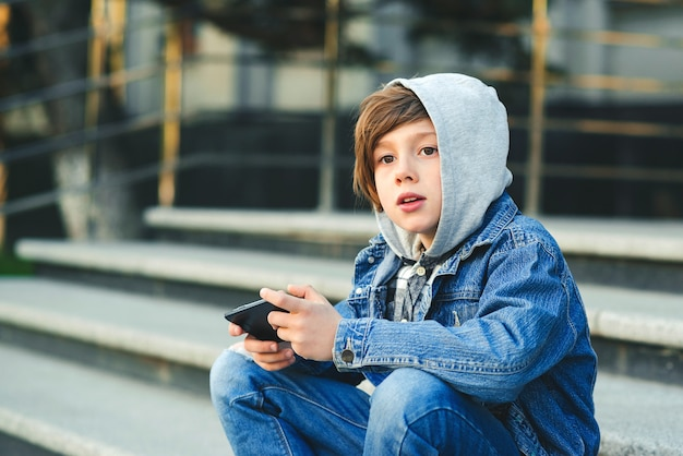 Schoolboy playing game on smartphone after school. technology, lifestyle, leisure. children addicted online games and videos. Premium Photo