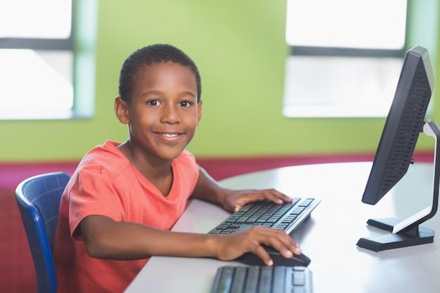 教室でコンピューターを使用している少年 Premium写真
